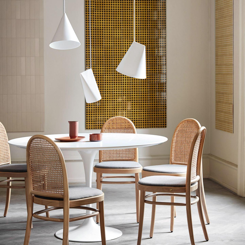 Drei Hängeleuchten in Hütchenform über einem runden, weißen Esstisch