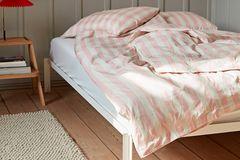 """Tischleuchte """"Matin"""" von Hay mit rotem Lampenschirm neben einem Bett mit rose-weißer Bettwäsche"""