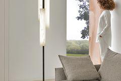 """Stehleuchte """"Black Note Triplet"""" von LZF Lamps neben einem grauen Stoffsofa im Wohnzimmer"""