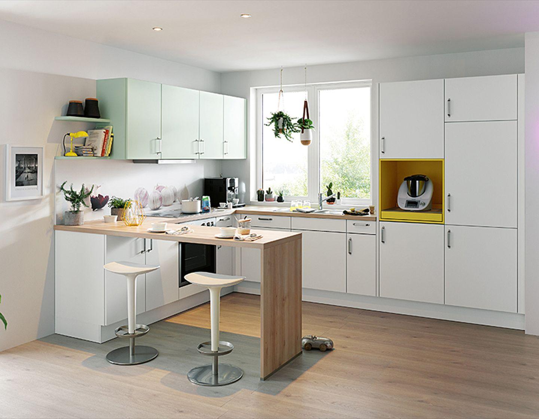 Kleine Küche mit weißen Fronten und Küchentresen aus Holz von Schüller.