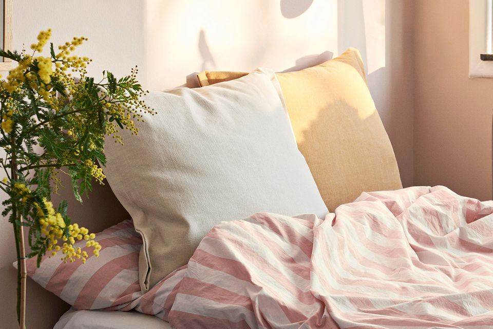"""Kissen """"Plica Tint"""" von Hay am kopfende eines Bettes"""