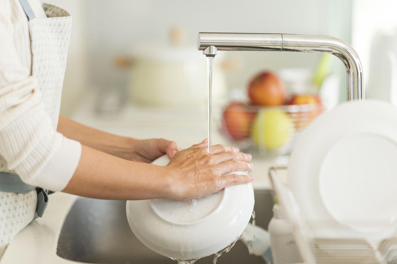 Frau, die einen Teller mit laufendem Wasser aus dem Hahn spült
