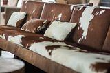 Polstermöbel mit braun-weißem Kühfell bezogen