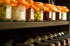 Lebensmittel lagern. Eingemachtes und Weinflaschen auf einem Kellerregal