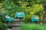 """Gartenstühle und Bank """"Net"""" von Nardi in Türkis in einem Garten"""