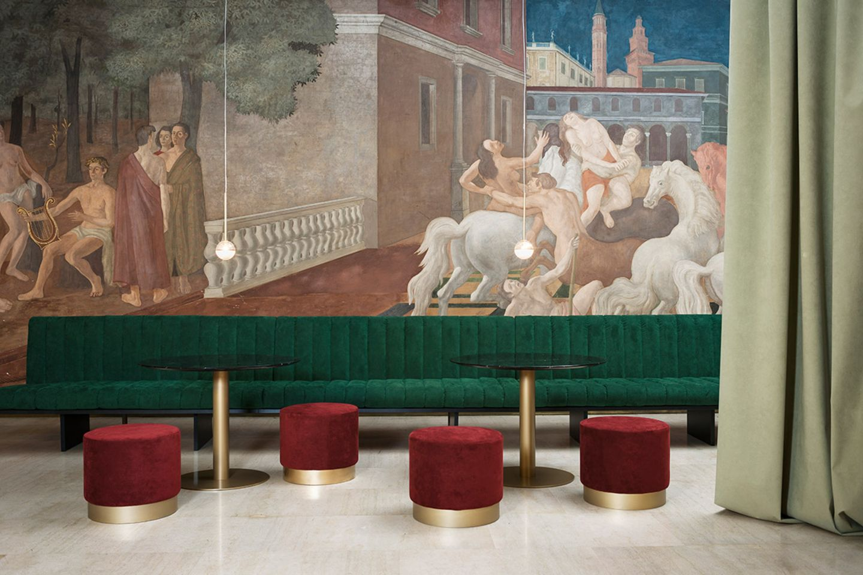 Grünes Sofa und rote Polsterhocker mit Bezügen aus Alcantara