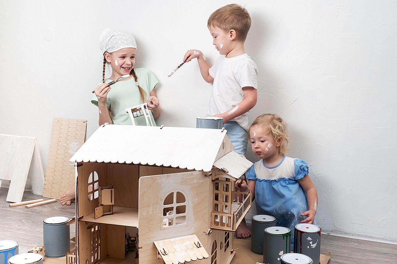 Kinder lackieren ein Spielhaus