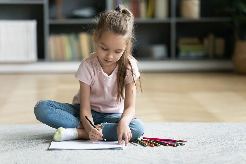 Ein Mädchen zeichnet am Boden sitzend