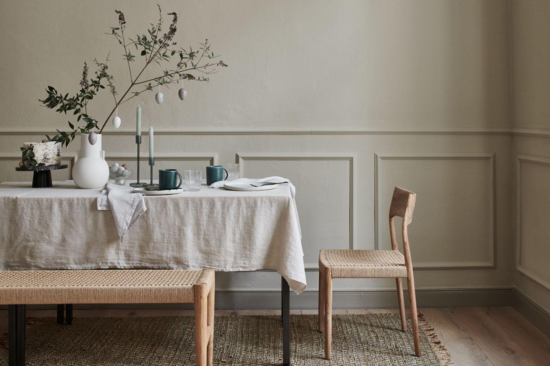 Tischdeko zu Ostern mit Zweigen, natürlicher Leinentischdecke in Beige und Möbeln aus Eichenholz und Flechtwerk