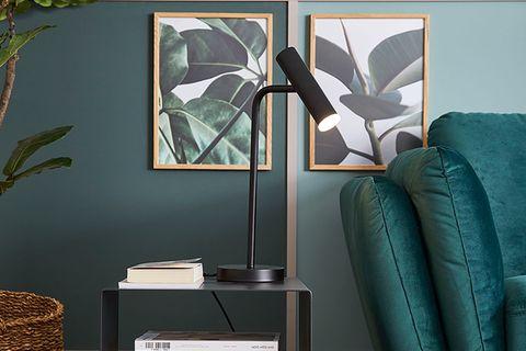"""Tischleuchte """"Stina"""" aus der SCHÖNER WOHNEN-Kollektion in Schwarz in einem Wohnzimmer in Grüntönen"""