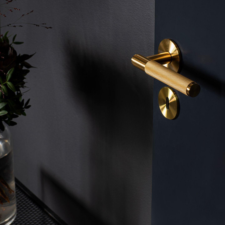 """Türklinke """"Door Leber Handle"""" aus massivem Messing an einer dunklen Tür"""