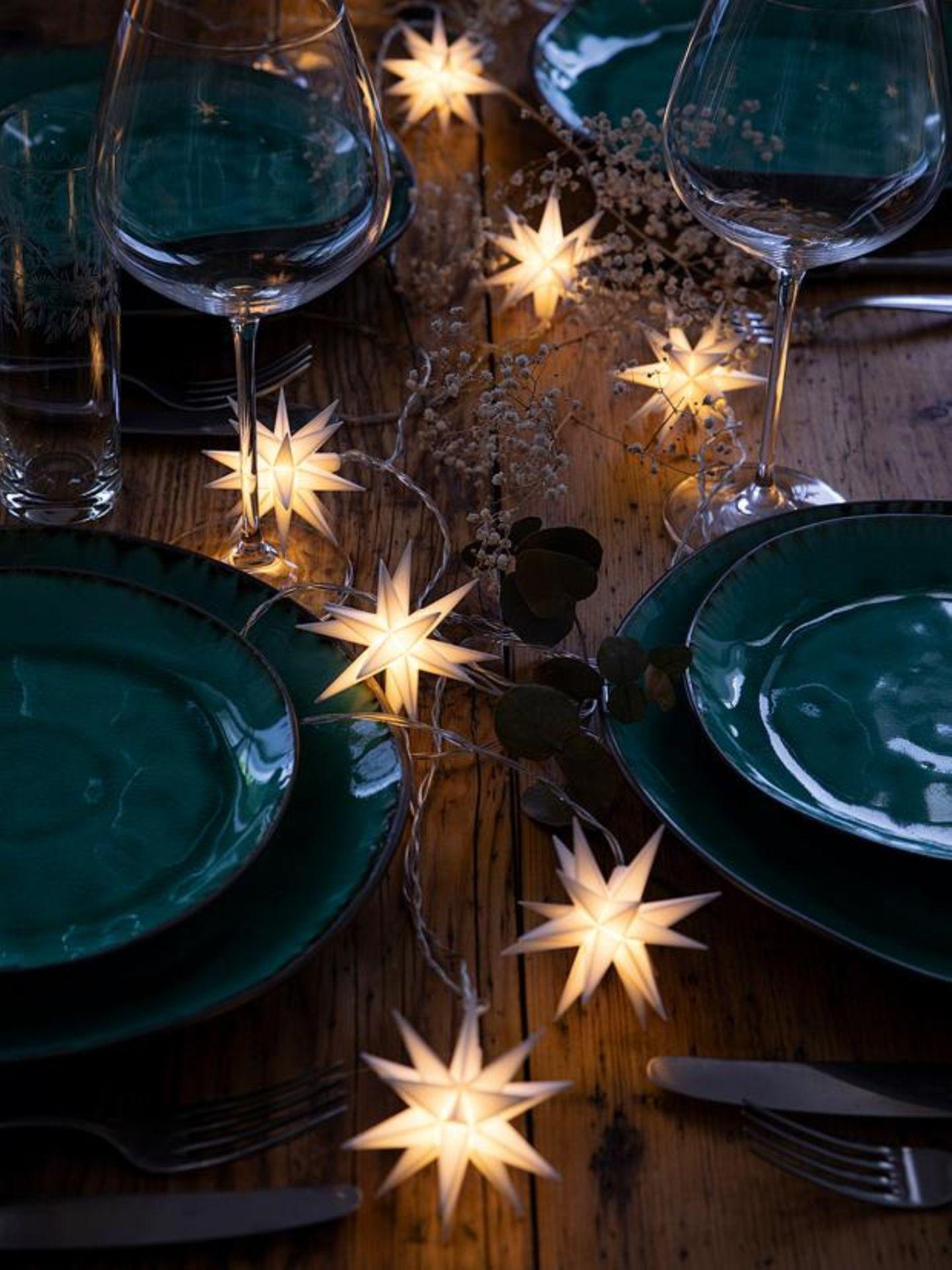 Lichterkette in Sternform auf einem festlich gedeckten Tisch mit dunkler Keramik.