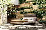 """Polsterbett """"Cama Slab"""" von Domkapa unter freiem Himmel vor einem vertikalen Garten stehend"""