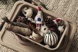 Weihnachtsbaumschmuck in Form von Anhängern und Kugeln in einer kleinen Kiste