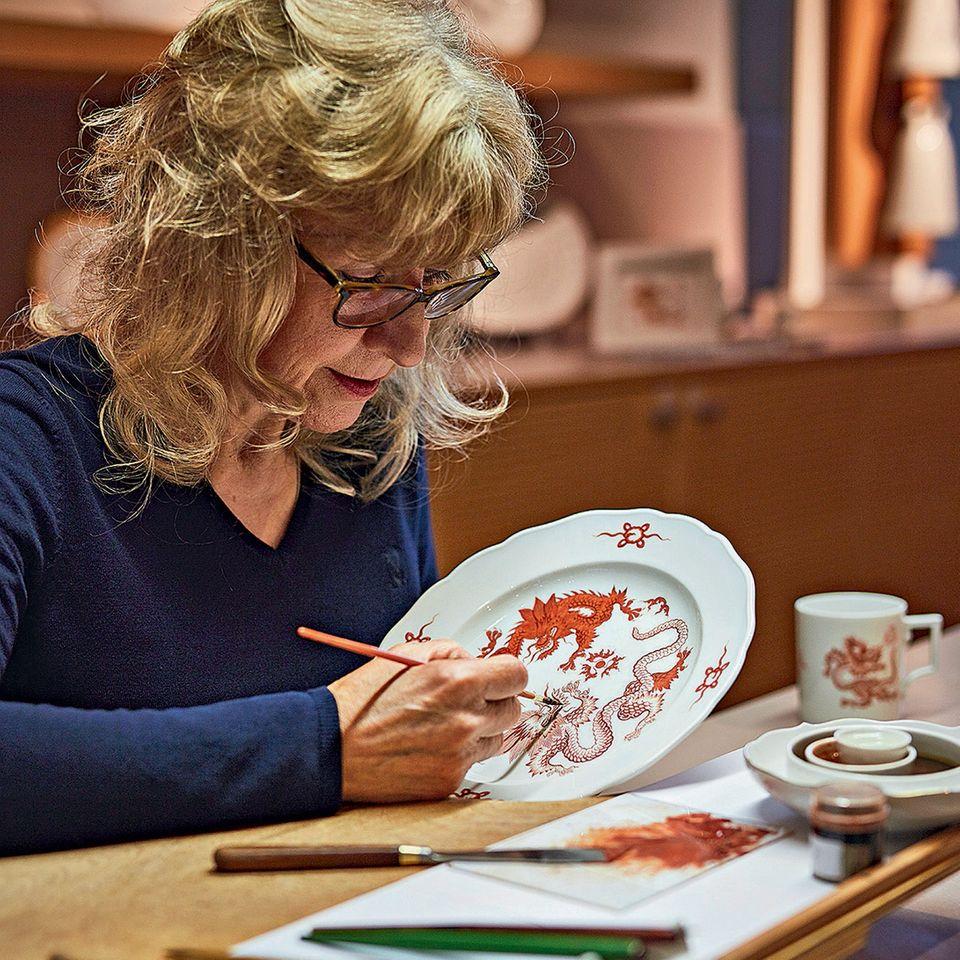 Sorgfältig trägt Christa Nettke das berühmte Ming-Drachen-Muster auf einen Teller auf