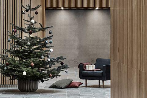 Geschmückter Weihnachtsbaum in einem mit Holz verkleideten Raum mit sehr hohen Decken