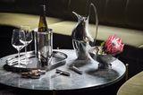 Gedeckter Tisch mit Gläsern, Blume, Flasche und Weinkühler