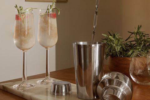 Tisch mit Cocktailgläsern und Mixer, im Hintergrund Pflanze und Bild