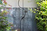 Schwarze, schlichte Freiluftdusche vor grauer Wand mit grünem Busch links und rechts
