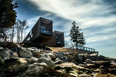 Man sieht ein spektakuläres Haus am Hang, mit Wald und Himmel