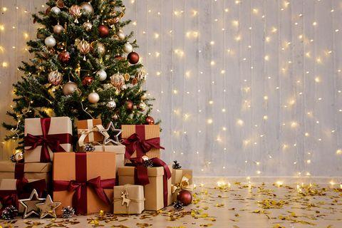 Stilvoll geschmückter Weihnachtsbaum umringt von zahlreichen Geschenken