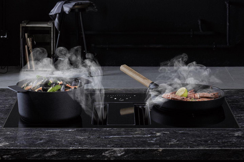 Küche mit schwarzer Arbeitsplatte, schwarzem Kochgeschirr sowie schwarzem Kochfeldabzug