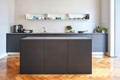 Schwarze Küche mit Eichenparkett und einer Arbeitsplatte aus 1 cm dickem Beton
