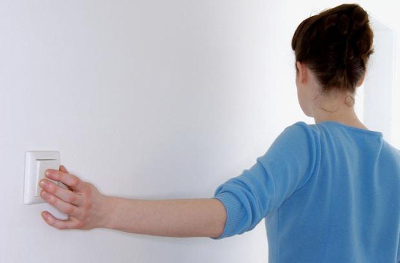 Frau steht an der Wand mit dem Rücken, Hand am Lichtschalter