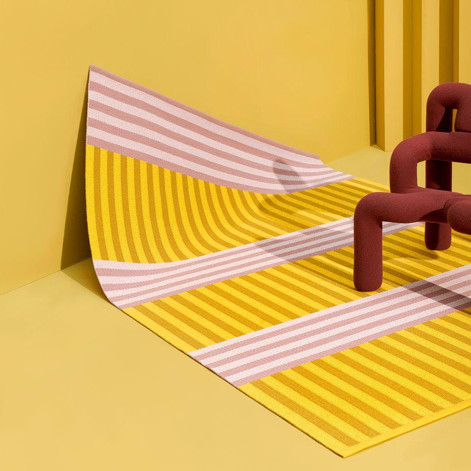 Gelber Teppich mit rosafarbenen Streifen in gelbem Raum