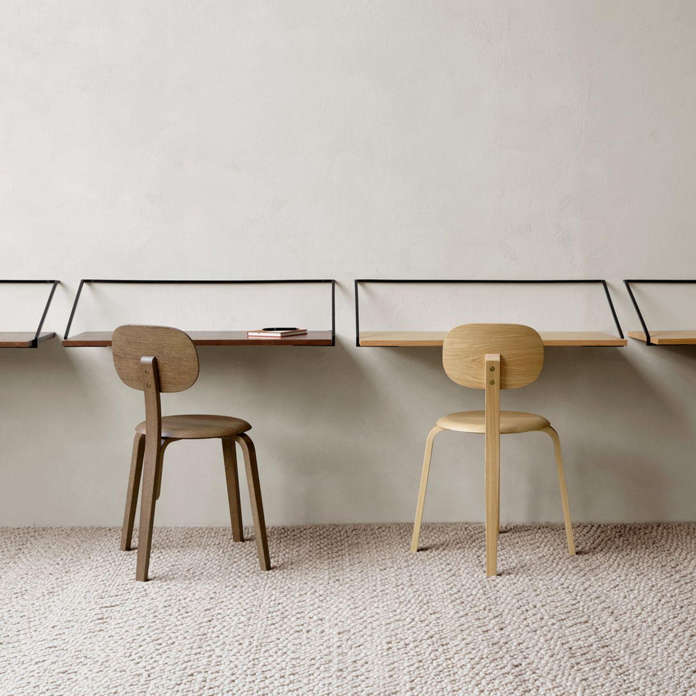 Wand-Schreibtische an der Wand mit zwei Stühlen davor