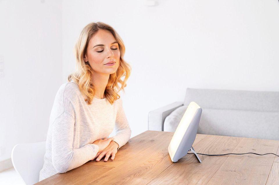 Frau sitzt am Tisch und schaut genussvoll in die Tageslichtleuchte