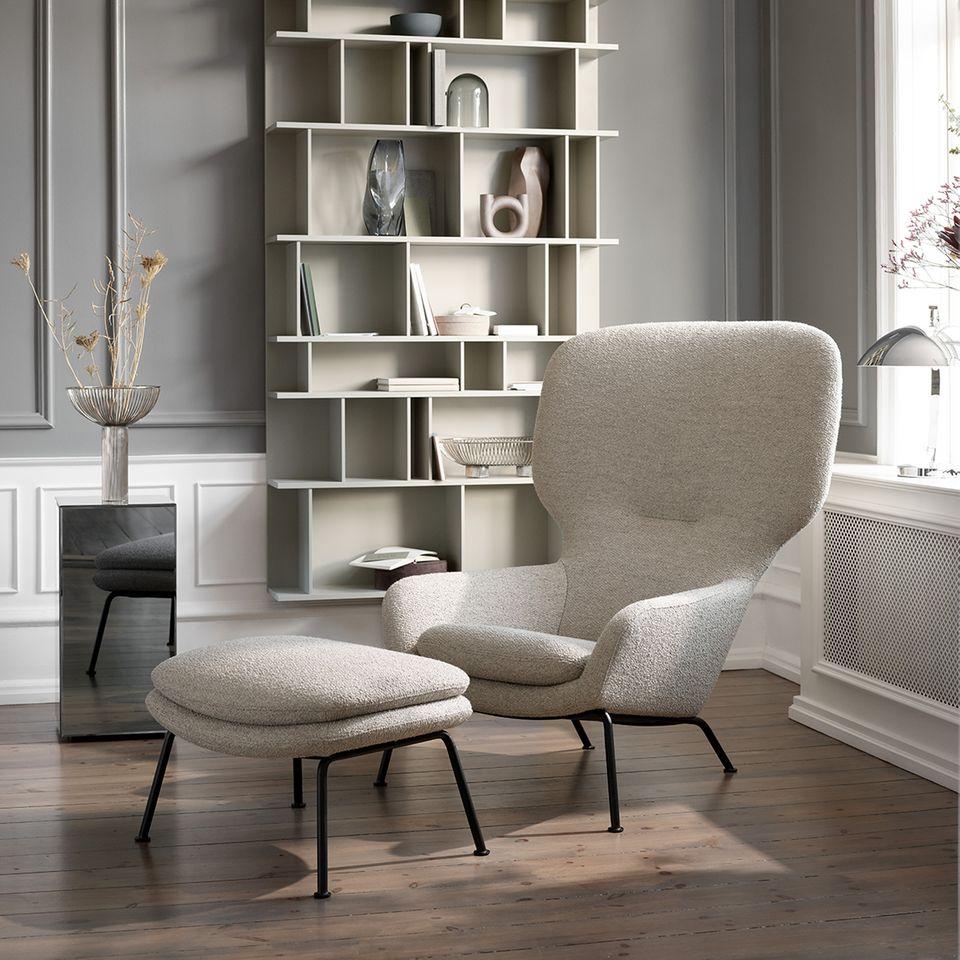 Sessel Dublin von BoConcept in grau vor einem Regal mit Büchern