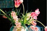 Rosefarbene Tulpen in einer Vase umgeben von Muffins und weiteren Kaffee- und Kuchenutensilien