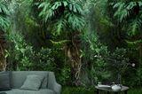 """Tapete """"Botanik"""" mit Dschungel-Feeling vor einem grünen Sofa und einem dunklen, kleinen Beistelltisch"""