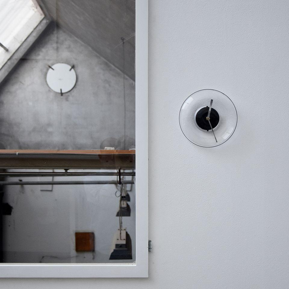 Uhr aus Glas hängt an einer Wand