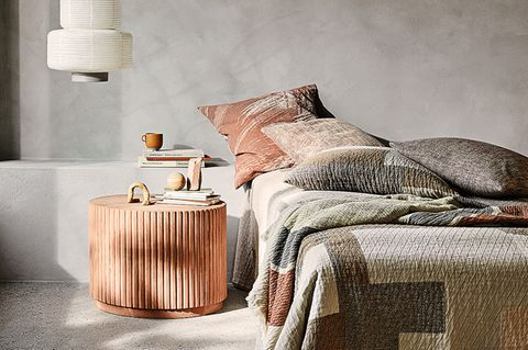 Bettwäsche in Erdtönen in einem Schlafzimmer in Grau.