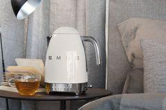 """Wasserkocher """"KLF04"""" von SMEG in Weiß auf einem Beistelltisch"""