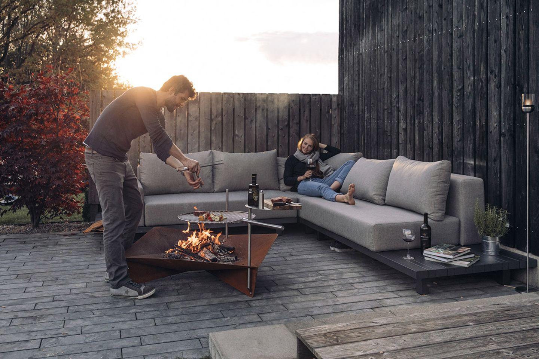 """Pärchen grillt mit der Feuerschale """"Triple""""von Höfats und chillt dabei auf einem Outdoorsofa"""