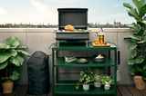"""Gasgrill """"Box"""" von Eva Solo auf einem grünen, dreistöckigen Tischchen auf einer Terrasse"""