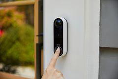 """Eine Frau betätigt Arlos """"Video Doorbell Wire Free"""" mit dem Zeigefinger"""