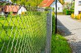 Maschendrahtzaun an einer Kopfsteinpflasterstraße in einem Dorf