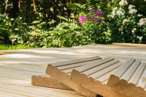 Holzterrasse. Im Hintergrund Blumen und Rasen