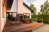 Holzterrasse auf zwei Ebenen mit einem Haus im Hintergrund.