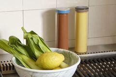 Salz- & Pfeffermühlen von Hay neben einer Schale mit Zitronen und Mangold