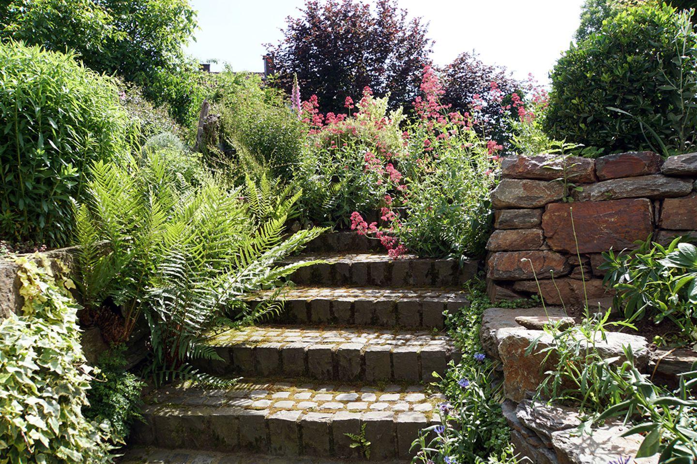 Gartentreppe aus Pflastersteinen im Sommer.