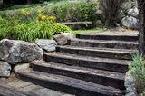 Gartentreppe aus Holzbohlen im Sommer.
