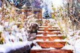 Gartentreppe aus Holz im Schnee.