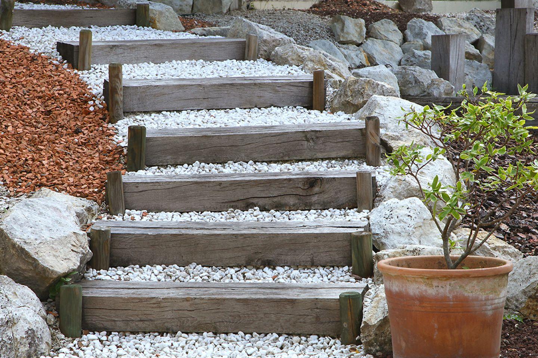 Gartentreppe mit Knüppelstufen und Kies.