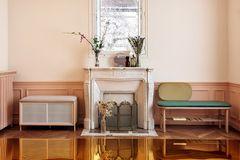 """Polsterbank """"Eustache"""" von Harto neben einem stilvoll dekorierten Kamin"""
