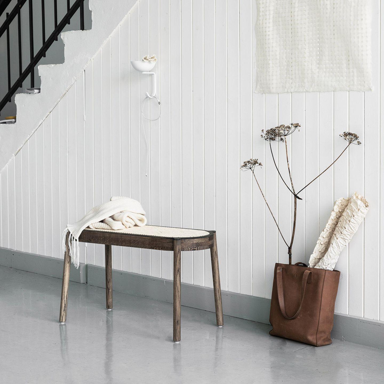 """Sitzbank """"Pal"""" von Norhern vor einer weißen Treppenwand, an der eine Ledertasche lehnt"""